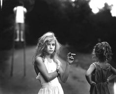 Candy Cigarette: Photographer Sally Mann captures one of her daughters in a defiant pose, staring down the lens at her mother, holding a bubblegum cigarette. [1989]