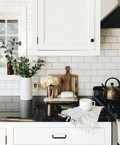 White pitcher with greenery in white kitchen with subway tiles