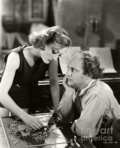 Joan Crawford helps one of the Three Stooges, Larry Fine, with a jigsaw puzzle. Photo comes from the 1933 film, Dancing Lady. (Sad Hill Archive / Bizarre Los Angeles)