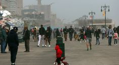 NEW YORK, NY - MAY 09:  People walk along the boardwalk at Coney Island following a week of cool and rainy weather on May 09,…
