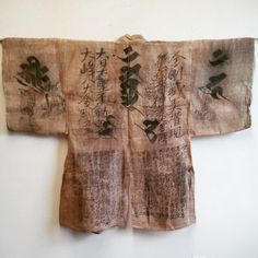 A hemp Japanese pilgrim's coat showing three prominent bonji characters, a kind of Sanskrit. The heart sutra is written on the bottom of the coat.