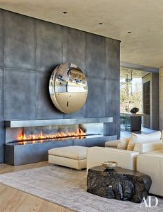 A mirrored Anish Kapoor sculpture animates the living room's blackened-steel fireplace surround | archdigest.com