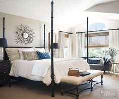 In a sea of whites and creamy beiges, black-stained furniture punctuates this master bedroom with a welcome jolt. An interplay of textures -- from the bamboo blinds to the flokati pillow -- and metallic finishes -- oil-rubbed bronze window hardware and chrome lamps -- give the room personality.