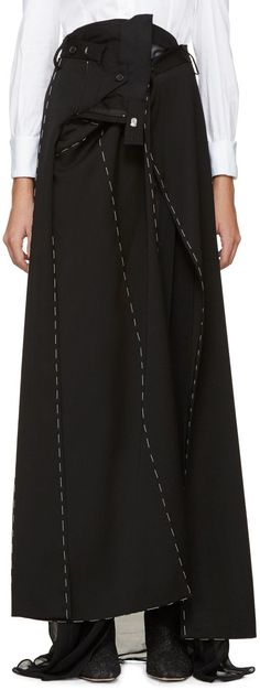 Long wool gabardine wrap skirt in black featuring modified trouser elements throughout. Panelled construction exposes semi-sheer tonal lining with patch pocket. Accent stitching throughout in white. Press-stud fastening and tie at waistband. Tonal stitching.