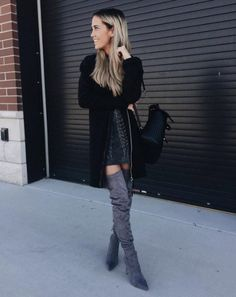 A long cardigan with a leather dress and over-the-knee boots.