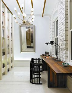 And interesting space - brick wall, shelving, high ceilings, light fixture and dark fabulous table and chairs, mirror. Mix of styles. apartment therapy