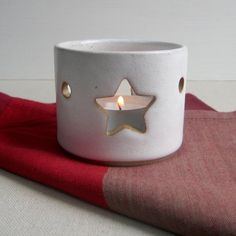 A lovely handmade tealight holder with star motif. This tealight holder features a cut-out design on opposite sides and casts a star-shaped glow to your room. Also suitable for short self-supporting candles. Hand-thrown in stoneware clay and decorated.