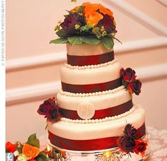 JK--The four-tiered wedding cake had two layers of cheese cake and two of carrot cake. Each tier was topped with a white chocolate mousse fondant-like icing and dressed with burgundy silk ribbon around the base.