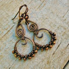 These all copper dangle earrings have been shaped, then hammered. Copper beads are wire wrapped along the bottom of the hoop. The hoop and swirl is topped with a smaller teardrop shape swirl, and wrapped together. The ear wires have been shaped, hardened, antiqued and polished smooth for comfort. The total length is approx 2 inches or 5 cm. E17484