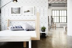 Contemporary Eclectic Bedroom: A sleek wood bed and bench with Eskayel wallpaper in an industrial lfot.
