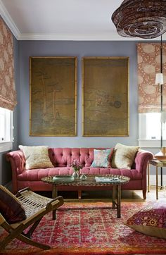 The den is anchored by a Chesterfield-style sofa covered in a raisin-colored linen and a vintage oriental rug. On the walls, Hranowsky used a gray lilac paint to set the backdrop for the rust and orange tones in the room.