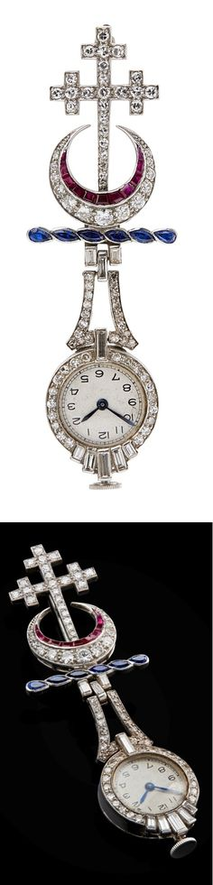 An early 20th century diamond and gem set pendant watch. Modelled as the arms for the Hannay family, set throughout with graduated round and eight cut diamonds, channel set square cut rubies and marquise cut sapphires, suspending an eight cut diamond set