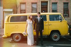 bride and groom standing on a city street in front of a vintage yellow van | photo: www.levkuperman.com