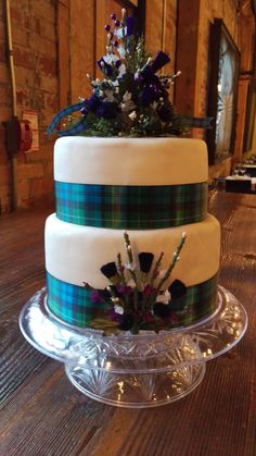 Chocolate stout cake layered with Bailey's Irish Cream buttercream. Covered in chocolate ganache and then white fondant. The silk flowers: Scottish thistle and heather, are from Scotland an the ribbon, custom made in California with the groom's family tartan. Wedding: November 20, 2015