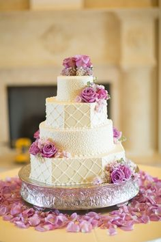 The bride's cake was done by Olexa's Cafe, Cakes, and Catering. It was a four tier cream cake with alternating designs. Mounded atop the cake was a cluster of flowers including cool water roses and lavender hydrangea. The same flowers were placed cascading down the cake | by Dorothy McDaniel's Flower Market; Unplugged Photography