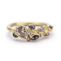 A cluster ring of rose cut grey diamonds and pear-shaped champagne diamond in yellow gold. Handmade in London, this is a unique engagement ring for an alternative bride.