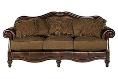 "The Claremore - Antique Sofa from Ashley Furniture HomeStore (AFHS.com). Flowing with the rich beauty of Old World design, the ""Claremore-Antique"" upholstery collection features the comfort of thick rolled arms wrapped in faux leather upholstery perfectly complementing the soft upholstery fabric in the seating area surrounding plush seating cushions to create elegant style without sacrificing the comfort you are looking for."