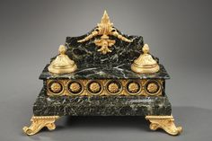 Green marble and gilt bronze inkstand. A rectangular green marble and gilt bronze inkstand composed of two inkwells hemmed with fluted frieze and crosspiece with their lids chiselled with foliages and pine cone atop, and a receptacle for feathers. Ormolu interlace, flowers, foliage and a central pattern adorned with acanthus leaves and flower buds decorate this inkstand resting on two front foliated feet and two ball-shaped feet ciseled with gadroon.   Circa :1860