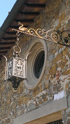 Florence Italy idea: Hang ornate lantern from a plant hangar outside of front door.