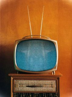 A vintage television with a turquoise screen against an orange wall. #TV