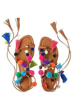 Pom Pom Wrap leather gladiator sandals with colorful pom pom, tassel, and lucky charm trim.