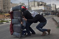 Masked Palestinians used a car seat as a shield during a protest outside Ofer, an Israeli military prison near the West Bank city of Ramallah, Tuesday. Palestinian protesters clashed with Israeli soldiers at a rally in support of four imprisoned Palestinians on hunger strike.