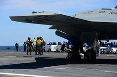ATLANTIC OCEAN (May 14, 2013) Sailors aboard the aircraft carrier USS George H.W. Bush (CVN 77) remove the chocks from an X-47B Unmanned Combat Air System (UCAS) demonstrator aircraft. George H.W. Bush is the first aircraft carrier to successfully catapult launch an unmanned aircraft from its flight deck. (U.S. Navy photo by Mass Communication Specialist 3rd Class Kevin J. Steinberg/Released) 130514-N-TB177-462