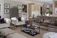 Chic living room features brown velvet sofa flanked by round black marble end tables facing a rectangular iron coffee table and a pair of stools upholstered in Stark antelope fabric across from a pair of white tufted accent chairs atop a jute rug.
