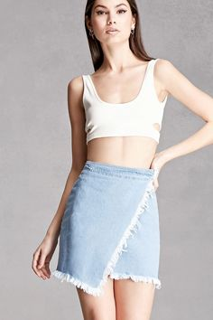 A denim mini skirt featuring a wrap style with an interior hidden button closure and a hook closure, an asymmetrical front hem, and frayed trim. This is an independent brand and not a Forever 21 branded item.