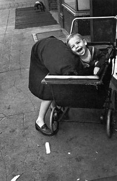 (♥) Photo by Helen Levitt. I LOVE this!  What was making him smile/laugh like that?  Was she tickling his feet?  Did she know they were taking her picture?  I can almost hear his laughter in this picture.