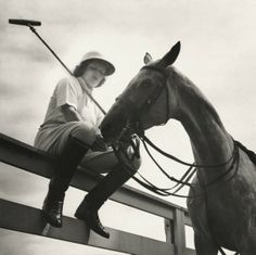 1937 : Judy Balding sitting on a fence, feeding an apple to her horse.