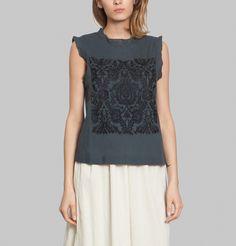 Top en coton couleur charbon, col arrondi avec bords plissés, manches débardeur à bords plissés, plastron brodé de coton noir, fermeture goutte et un bouton au