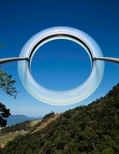 mariko mori sites luminous ring at the peak of a cascading waterfall in brazil