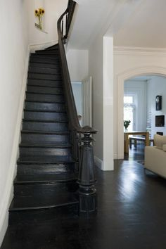 Roberts dyed the original battered floors using a mix of half dark mocha and half black and painted the stairs and balusters in high-gloss floor paint.