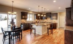 We love the unique look of this @lennarminnesota kitchen with dark wood cabinets and a white island!