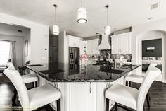 Painted maple cabinets make a stark contrast to dark quartz countertops and dark porcelain plank tiles.  Modern dream kitchen!  Visit https://www.zelmarkitchendesigns.com for more design ideas.