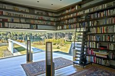 What I like about this unique layout is the books are not exposed to direct sunlight, yet the room retains an open atmosphere because of the wall-to-wall windows. Very creative!