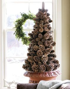 Easy to make pinecone tree. One planter, one styrofoam cone, some pinecones, wire, and glue and I'll be set! Add some lights