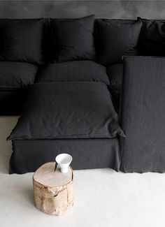 "Black ""Ghost"" sofa Paola Navone.    Downside of black sofa - the lord of the manner will have it covered in ginger fur in less than 24hr.  The maintenance will be unending."