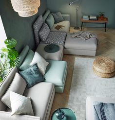A sofa combination in beige and green, that seats five, consisting of corner modules, one-seat modules and footstools with storage.