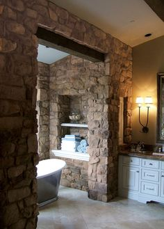 Rustic Stone Bathroom. Have the stone wrap around and form a shower...