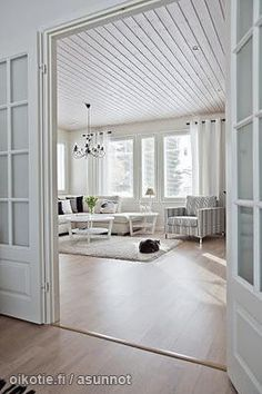 French doors open into the open floor plan with lots of windows and simple clean decor. Very light and welcoming.