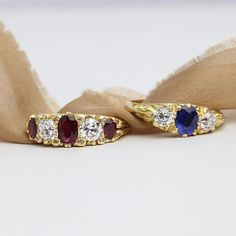 This three stone sapphire and diamond ring (on the right) is made in a Victorian design. The 19th century style known as a carved half hoop features intricate and expert carving in a scroll pattern. The 18 carat yellow gold ring is set with a bright blue
