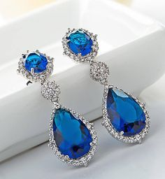 *Free shipping worldwide* Bold and colourful, these eye-catching teardrop earrings features synthetic sapphire framed by a dazzling halo of pavé-set cubic zirconia.   bridal earrings   wedding earrings   bridesmaid earrings   prom earrings   silver earrings   sapphire blue earrings   bridal jewelry   wedding jewelry   prom jewelry   bridal jewellery   wedding jewellery   prom jewellery
