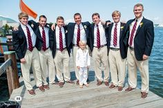 Groom and his groomsmen sport true nautical fashion in their boat shoes, khakis, navy sport jackets, and red striped ties. All groomsmen wore a boutonniere of yellow billy balls wrapped in striped ribbon.  Flowers by www.intrigue-designs.com, photography by www.hamiltonphotography.net, venue by www.annapolisyc.com.