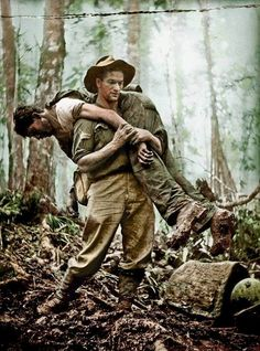 This famous photograph by war correspondent Gordon Short captures Australian Leslie 'Bull' Allen rescuing a wounded American soldier on Mount Tambu, New Guinea, 30th of July 1943. During an American assault against the Japanese on Mount Tambu, more than 50 US soldiers were injured. Two medics were killed trying to retrieve them.:
