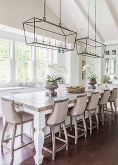 french style dining area in kitchen with linen covered wooden bar stools and lantern rectangular pendant lights above table