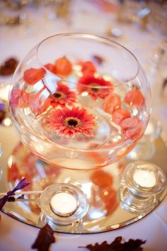 Single red gerberas and petals in fishbowls filled with water as centrepeices, surrounded by tea light candles and oak leaves scattered on table.