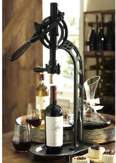 Modeled after a vintage professional wine opener we saw at a vineyard, our tabletop version securely holds a wine bottle in place for uncorking. 14″ wide x 9″ deep x 265″ high Made of steel metal with a bronze finish and a rubber wood handle Brand: Pottery Barn Retailer: Pottery-Barn