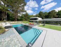 L'esprit design par l'esprit piscine   12 x 4,5 m Revêtement gris clair et noir Escalier d'angle intérieur avec banquette sur la largeur Margelles et plage en grès cérame
